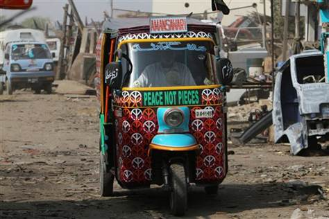 In this Saturday, Feb. 2, 2013 photo, a Pakistani rickshaw driver makes his way through slums of Karachi, Pakistan.